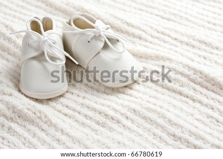 A pair of baby shoes sitting on baby blanket with copy space. - stock photo