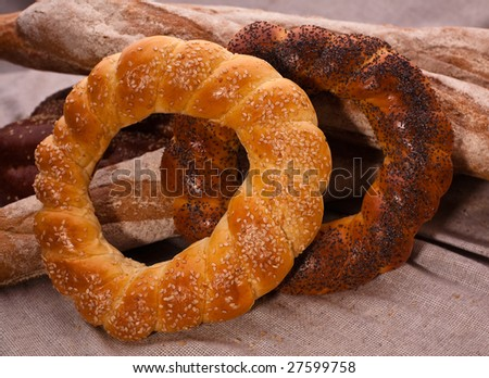 A pair of bagels covered with sesame and papaver together with baguettes on the canvas tablecloth