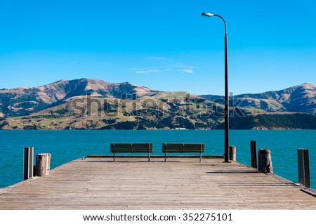 A pair of benches on the wooden pier in Akaroa, South Island, New Zealand - stock photo