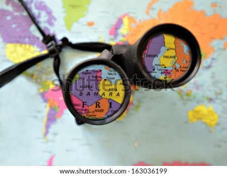 A pair of binoculars on top of a world map.  Countries highlighted in the lens. - stock photo