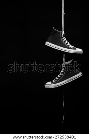 A pair of black and white sneakers hanging by their laces in front of a black background - stock photo