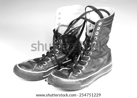 A pair of black canvas sneakers on white background - stock photo