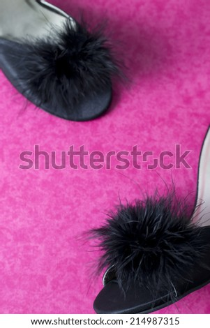 A pair of black mule slipper shoes on pink fuchsia, background. - stock photo