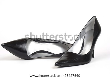 A pair of black women's high-heel shoes against a white background, one shoe standing, one shoe lying on side - stock photo