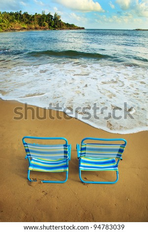A pair of blue and green striped beach chairs close to the water on a beautiful, sandy beach.  There is a blue sky with clouds, green foliage and beautiful blue water of the ocean. - stock photo