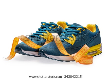A pair of blue sports shoes with measurement tape on white background - stock photo