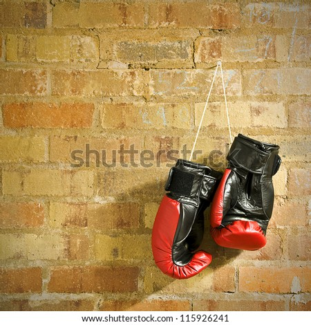 a pair of boxing gloves hanging on a wall - stock photo