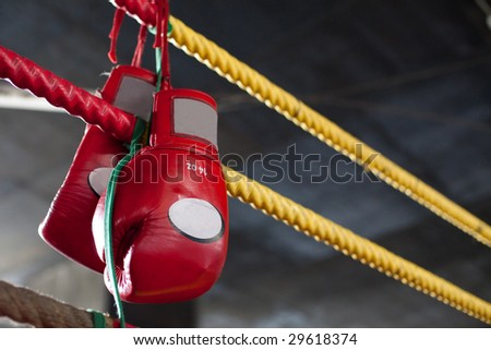 A pair of bright red Muay Thai boxing gloves hangs off the boxing ring in a slum camp - stock photo