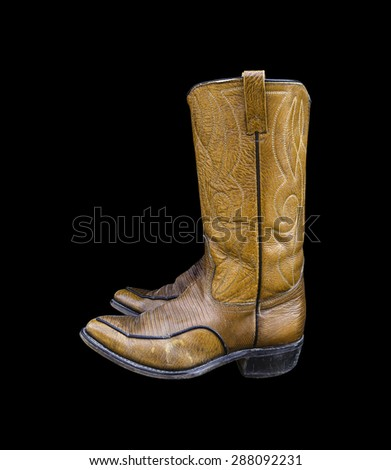 A pair of brown cowboy boots isolated on a black background.