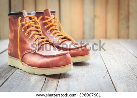 A pair of brown leather boots on wooden floor, selective focus  - stock photo