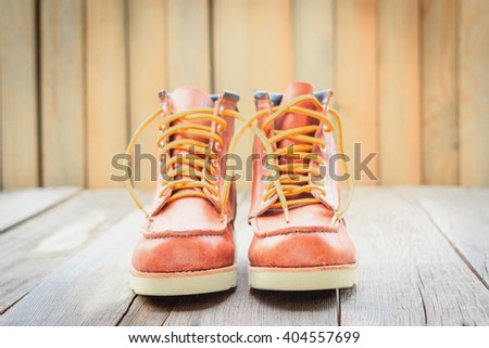 A pair of brown leather boots with laces placed on wooden floor - stock photo
