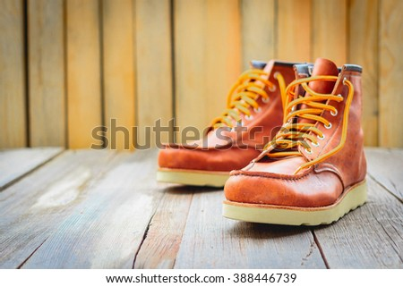 A pair of brown leather boots with laces placed on wooden floor, selective focus - stock photo