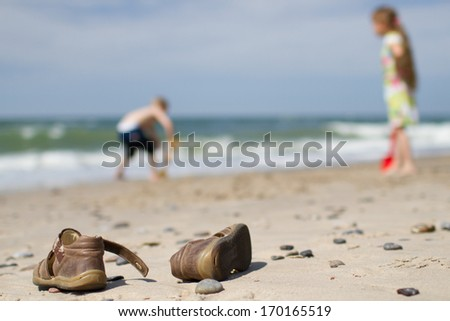A pair of brown leather sandals placed casually on a somewhat rocky Northern European beach. Blurred background with a boy and a girl digging in the sand. - stock photo