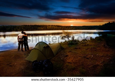 A pair of campers with a tent set against a beautiful sunset lake landscape