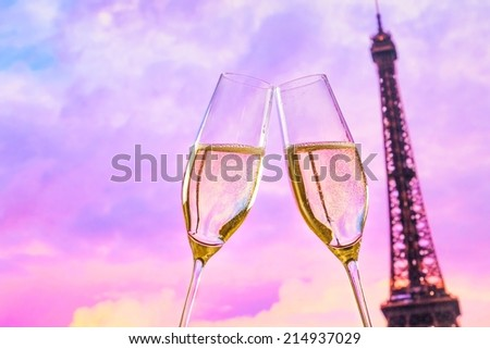 a pair of champagne flutes with golden bubbles make cheers on sunset blur tower Eiffel background valentine day concept - stock photo