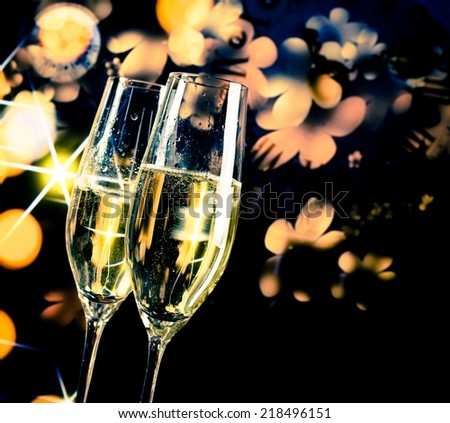 a pair of champagne flutes with golden bubbles on golden and dark light background with space for text - stock photo