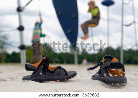 A pair of children-outdoor-shoes standing in the sand of a playground with climbing kids. - stock photo