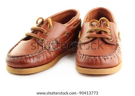 A pair of children's boat shoes or top-siders, isolated on a white background. - stock photo