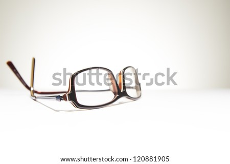 A pair of classic framed reading glasses resting on a white background with space for text - stock photo