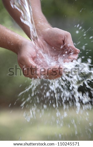 A pair of cupped hands catch a big spash of fresh water outside. - stock photo