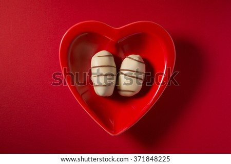 A pair of date chocolates in a red heart shaped dish. Arabic valentines day concept. View from top. - stock photo