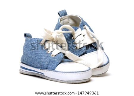 A pair of denim baby shoes for the toddlers feet. - stock photo