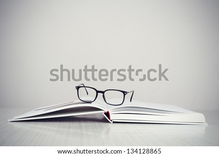 A pair of designer glasses on an opened coffee table book. - stock photo