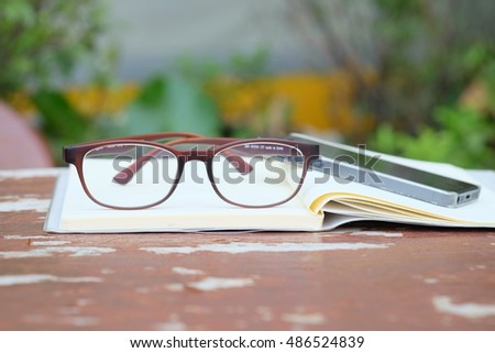 A pair of designer glasses on an opened old table book.