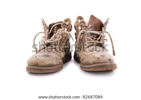 A pair of dirty brown boots. - stock photo