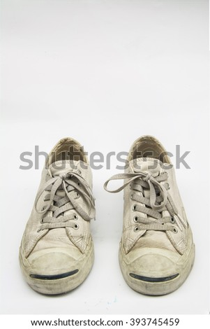 a pair of dirty sneakers isolated on white.
