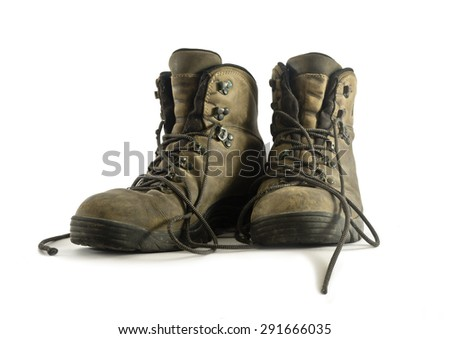 A pair of dirty worn hiking boots closeup on white background. Boots have grey leather upper and rubber soles. Shoelaces are loose. Image shows front view of boots with lacing, upper and tongue.  - stock photo