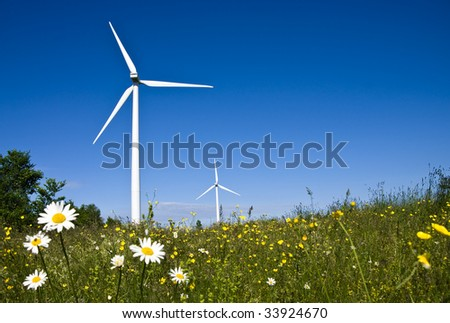 A pair of energy producing wind turbines - windmills - in a field. Complete with green meadow, daisy flowers and blue sky. - stock photo
