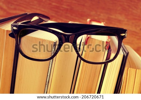 a pair of eyeglasses on a pile of books, with a retro effect - stock photo