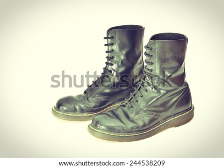 A pair of 10 eyelet classic black lace-up combat boots - vintage processes - stock photo