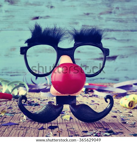 a pair of fake black glasses with eyebrows, a red clown nose and a mustache forming the face of a man on a rustic wooden surface full of confetti - stock photo