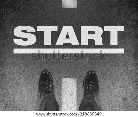 A pair of feet on a tarmac road with the word Start. A concept of starting point.  - stock photo