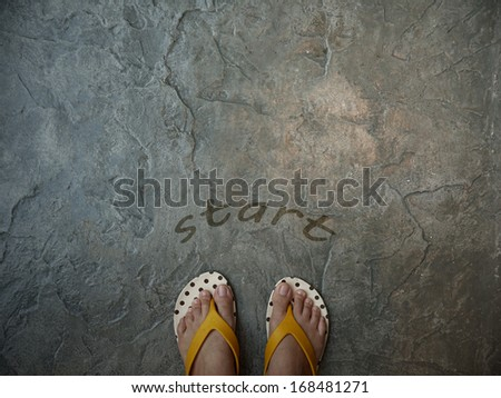 A pair of feet on floor with word start for the concept of starting point - stock photo