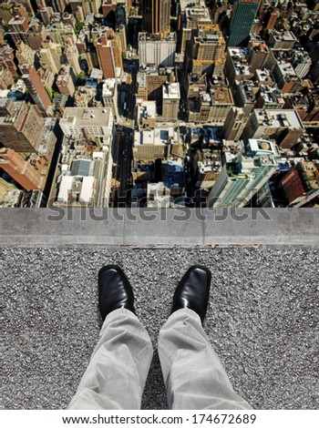 A pair of feet on the edge of a tall building ledge looking down into a city of highrise.  - stock photo