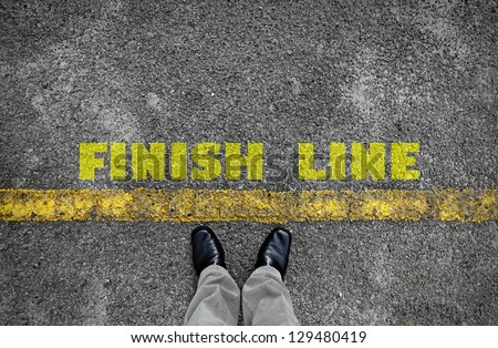 A pair of feet standing at the edge of a yellow line on an asphalt road with a yellow print of the word Finish Line for the concept of accomplishment. - stock photo