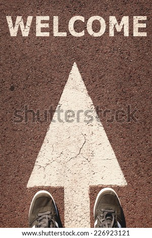 A pair of feet standing on street, white direction arrow, welcome concept. Toned concept , low contrast. - stock photo