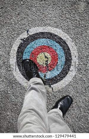 A pair of feet stepping onto a colorful bull eye target symbol on an asphalt road for the concept of walking into the line of fire. - stock photo