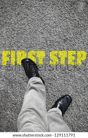 A pair of feet taking a step on an asphalt road across a yellow print of the word First Step for the concept of achievement. - stock photo