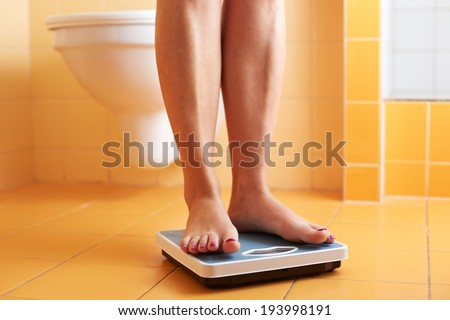 A pair of female feet standing on a bathroom scale - stock photo