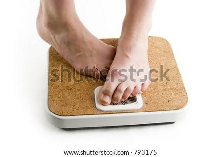 A pair of female feet standing on a bathroom scale looking shy about the weight - stock photo