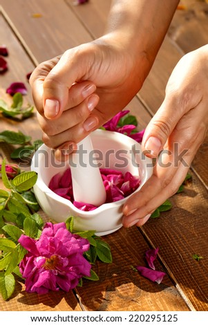 A pair of female hands holding a pestle and mortar grinding rose petals