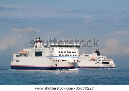 A pair of ferry ships cruising the calm sea, summer time - stock photo