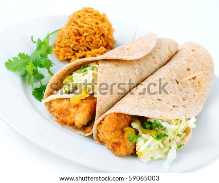 A pair of fish tacos served with spanish rice on a white background