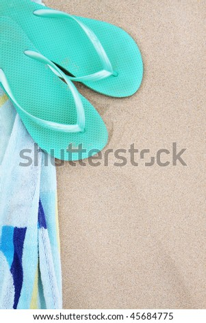 A pair of flip flops and beach towel on the sand. - stock photo
