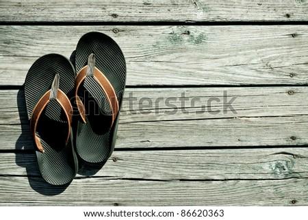 A pair of flip-flops on outside deck await summer fun - stock photo