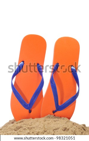 a pair of flip-flops on the sand on a white background - stock photo